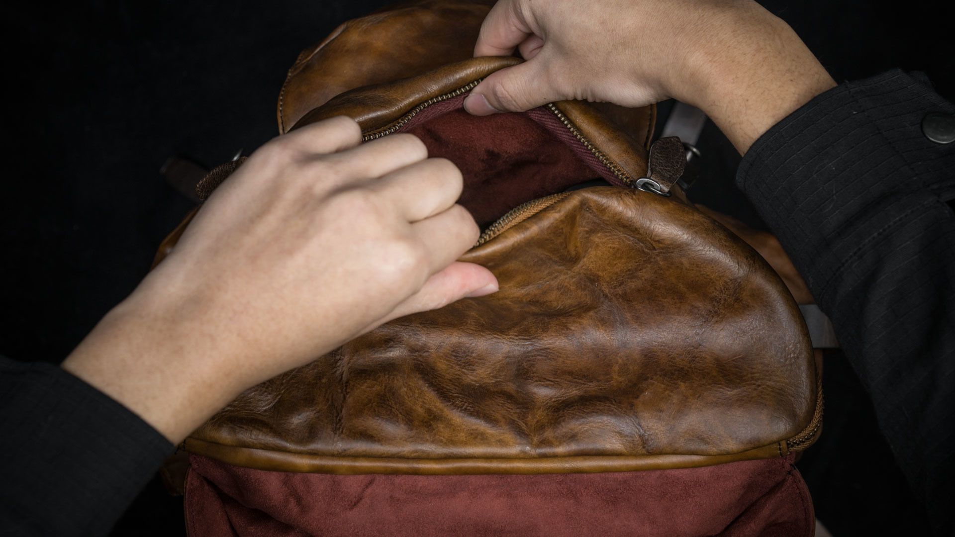 Oval shaped zippered top flap.